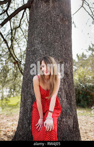 Young smiling woman with red dress leaning towards the camera - Stock Photo