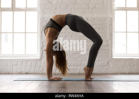 attractive woman practicing yoga urdhva dhanurasana pose