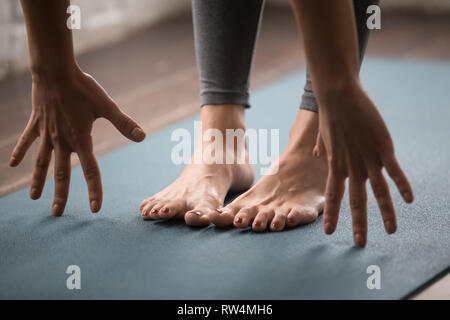 Woman practicing yoga, uttanasana pose, Head to knees close up - Stock Photo