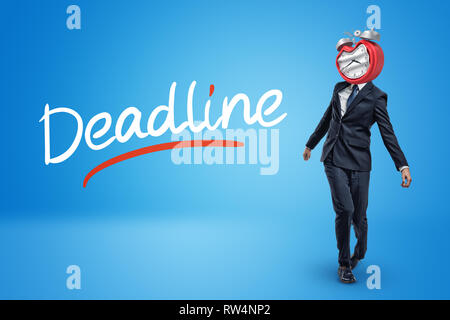 Staggering businessman with melting clock instead of head and DEADLINE sign on blue background - Stock Photo