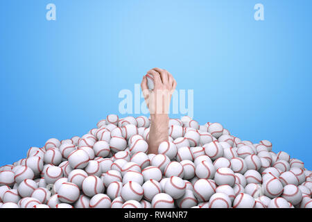 Man's hand holding a baseball, emerging from under a big pile of baseballs. - Stock Photo