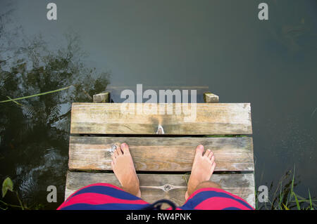 Top view of male legs and feet standing near river on wooden bridge - Stock Photo
