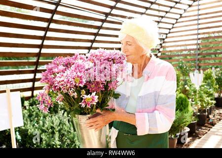 Senior Gardener Smelling Flowers - Stock Photo