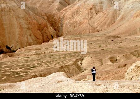 A solitary man walks a trail in barren desert hills. - Stock Photo