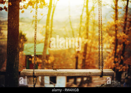 Old wooden rocking chair on chains in wood, late fall season. - Stock Photo