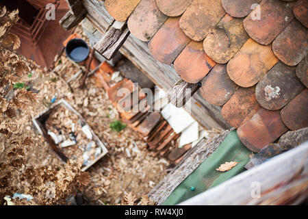 View from an old roof on tiles and backyard garden full of old things in blur. Village lifestyle details. - Stock Photo
