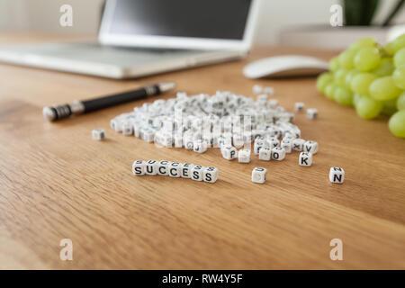 Success word written on cube shape white blocks on wooden Busine - Stock Photo