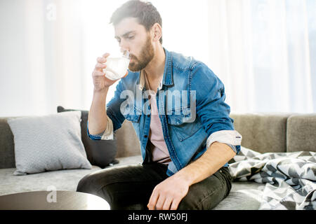 Man drinking some medicines feeling bad or having hangover after the alcohol party, sitting on the couch at home - Stock Photo