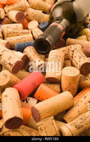 Assorted wine bottle corks and empty bottle of red wine - Stock Photo
