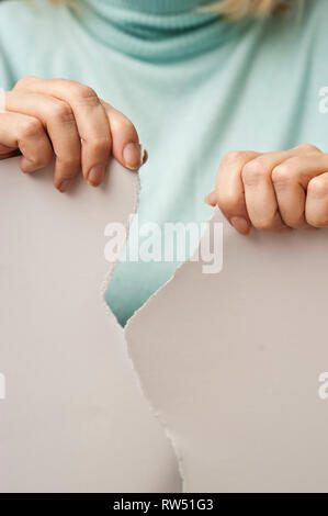 sequence images of the hands of a woman ripping a paper in half - Stock Photo