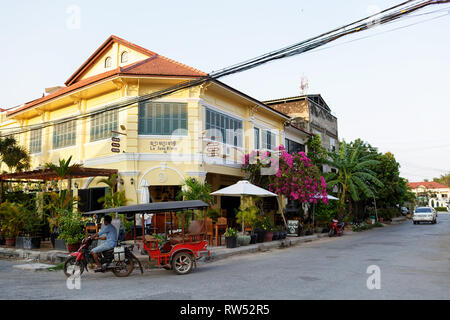 Street scene, old yellow french colonial architecture buildings in kampot downtown street and a tuk tuk cambodia - Stock Photo