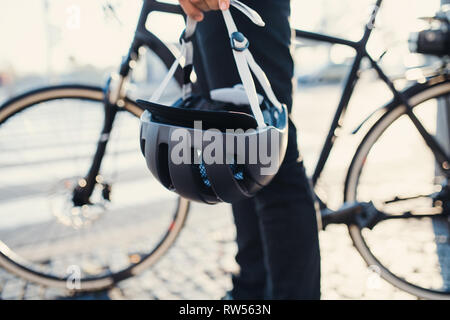 Midsection of unrecognizable commuter with electric bicycle and helmet traveling in city. - Stock Photo