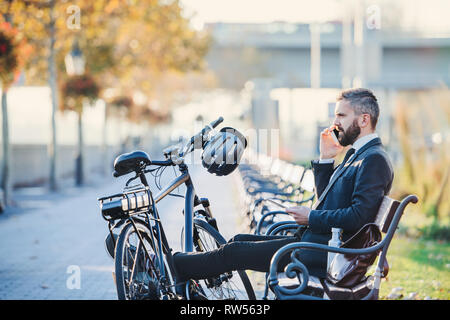 A side view of businessman commuter with smartphone and bicycle sitting on bench in city, making a phone call. - Stock Photo