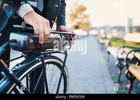 A midsection of businessman commuter setting up electric bicycle when traveling home from work in city. - Stock Photo