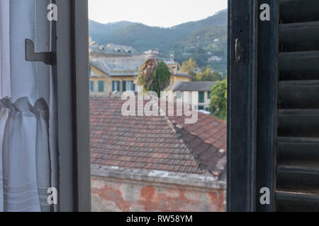 Italian town view from a half opened window with a wooden shutter - Stock Photo