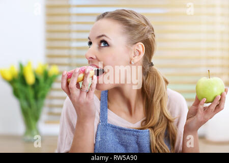 Adult woman choosing between apple and donut in the kitchen - Stock Photo
