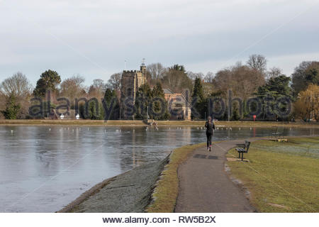 Lady Running Along Perimeter Path of Stowe Pool with Frozen Water and St Chad's Church in Background, Lichfield, England, UK. - Stock Photo