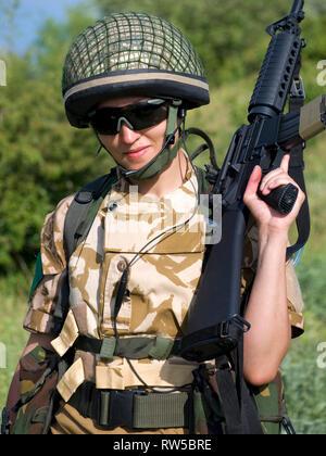 Female British soldier in desert uniform holding her rifle. - Stock Photo