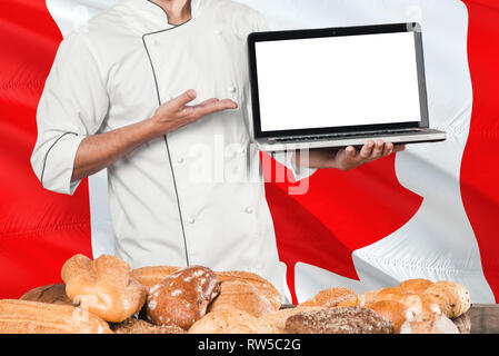 Canadian Baker holding laptop on Canada flag and breads background. Chef wearing uniform pointing blank screen for copy space. - Stock Photo