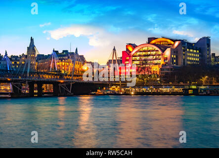 Night view of the Embankment tube station and blackfriars bridge reflected in the Thames river in London, UK - Stock Photo