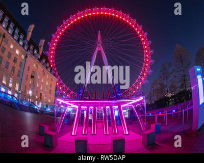 London, England, UK - February 27, 2019: Night scene with wide view of the famous London Eye against the sky full of stars, illuminated at night - Stock Photo