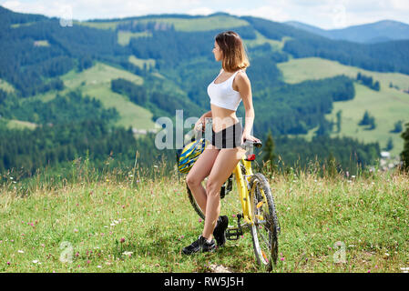 Side view of athlete young woman cyclist posing with yellow mountain bicycle on a grass, enjoying sunny day. Mountains, forests on the blurred background. Outdoor sport activity, lifestyle concept - Stock Photo