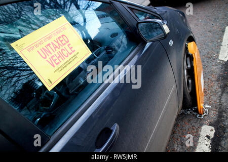 warning label and wheel clamp on untaxed vehicle car clamped on a street in the uk - Stock Photo