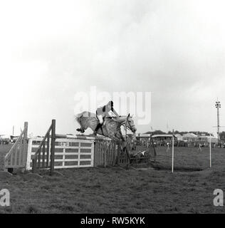 1967, teenage girl rider on a horse jumping a fence or obstacle at the Bucks county show, Engand, UK.