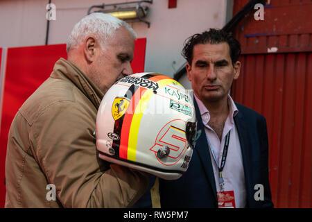 Barcelona, Spain. 1st March, 2019 - Racing Helmet of Sebastian Vettel  with 5 of Scuderia Ferrari SF90 held by tv presenter at F1 Winter Test. - Stock Photo