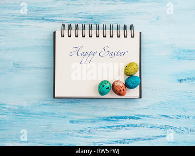 Multicolored, bright Easter eggs, sketchbook page on a blue background. Top view, close-up. Preparation for the holiday. Congratulations for loved one - Stock Photo