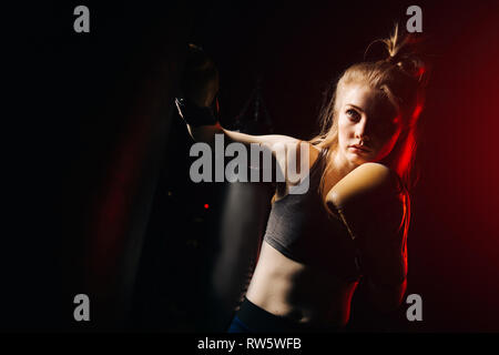 Serious female boxer in boxing gloves practicing near bag on black and red background - Stock Photo
