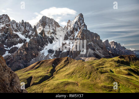 Cimon della Pala (also called 'The Matterhorn of the Dolomites') with snow covered peaks grassy fields in foreground. San Martino di Castrozza, Italy. - Stock Photo