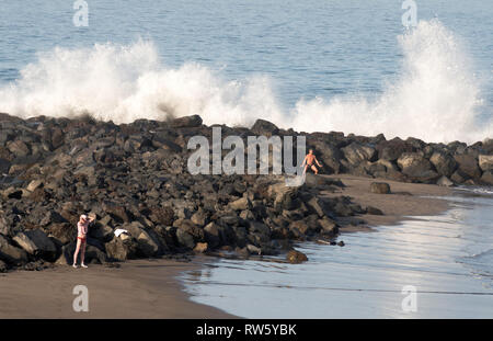 People exercising on the beach while waves crash into rocks behind, Costa Adeje, Tenerife, Canary Islands. - Stock Photo