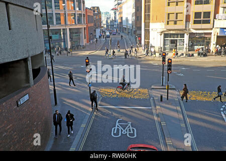 Bicycle lane, cyclist on a bike on a pedestrian crossing and pedestrians in the street near the Barbican station City of London UK  KATHY DEWITT - Stock Photo