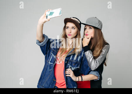 Two swag sisters taking self portrait on call phone. - Stock Photo