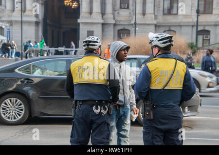 Philadelphia, Pennsylvania - February 5, 2019: Black male is seen here arguing with two Philadelphia police officers during an demonstration in front  - Stock Photo