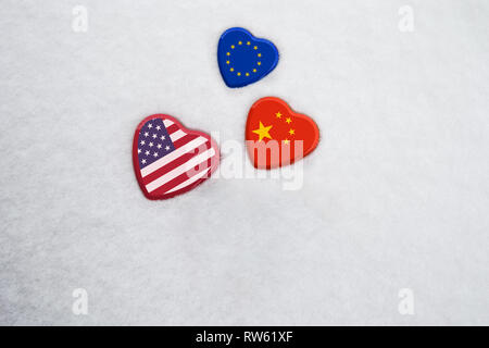 USA, China, EU national flags on heart shaped boxes laying on snow close together. Concept of economic political relationships and partnerships - Stock Photo