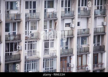 Inhabited, old and neglected communist era block of flats - Stock Photo