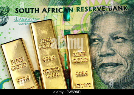 A macro image of a green ten rand note from South Africa with three small gold bars - Stock Photo