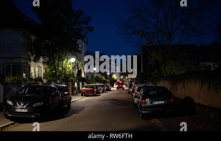 Strasbourg, France - Cot 13, 2018: French street at dusk with multiple houses and cars parked on the trottoir - Stock Photo