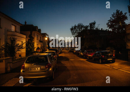 Strasbourg, France - Oct 13, 2018: French street at dusk with multiple cars parked on walkside - Stock Photo