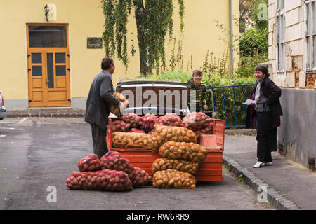A Romanian family loading up a trailer with bags of red and white potatoes. Brasov, Romania, Eastern Europe - Stock Photo