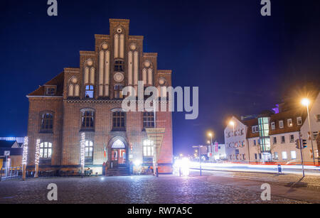 Wismar, Germany. 24th Feb, 2019. Renovated historic warehouse buildings can be seen in the city harbour after dark and are partly reflected in the water. Credit: Jens Büttner/dpa-Zentralbild/ZB/dpa/Alamy Live News - Stock Photo