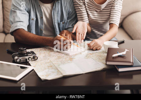 Couple planning vacation, making notes in diary - Stock Photo