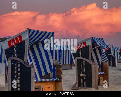 two beach chairs in burning sky sunset on island Norderney, germany - Stock Photo