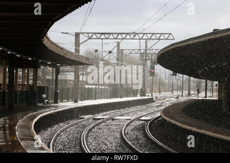 View south from Carnforth station towards the West Coast Main Line during a heavy rain shower with the rain back-lit by sunshine reflecting off rails. - Stock Photo