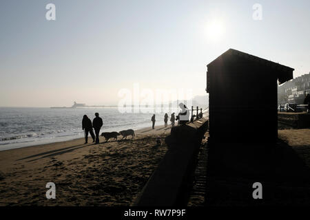 Dogs and people walking along Sandown beach on a lazy Sunday afternoon silhouetted in bright hazy winter sunshine. - Stock Photo