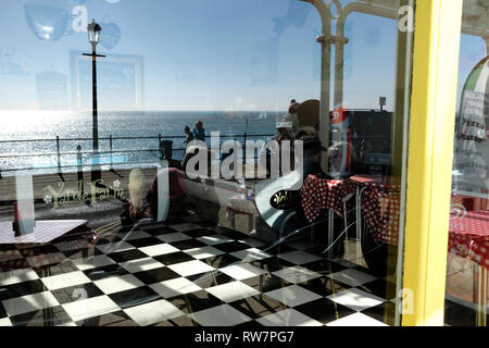 A seafront ice cream parlour, Ventnor, Isle of Wight, showing black and white chequered tiled floor and reflections of beach front promenaders and sea. - Stock Photo