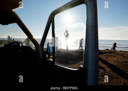 Silhouette of a man framed by a van window eating an ice cream cone on the headland at Compton Bay, Isle of Wight, England, British Isles, UK. - Stock Photo