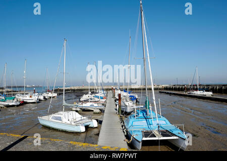 Ryde Harbour on the Isle of Wight at low tide showing yachts and motor boats grounded on the seabed. - Stock Photo